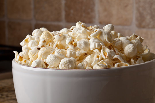 Close-up of a vintage ceramic bowl with olive oil organic popcorn on granite counter
