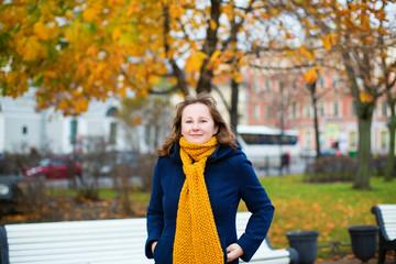 Cheerful girl in yellow scarf enjoying fall day