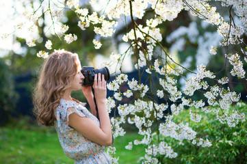 Beautiful woman in blooming cherry garden