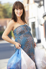 Pregnant woman with heavy shopping