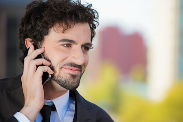 Businessman talking on a phone outside outdoor background