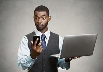 Portrait businessman holding smartphone, computer multitasking
