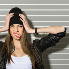 Hipster teenage girl making faces and holding her head