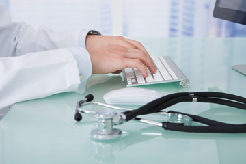 Doctor Using Computer At Desk In Clinic