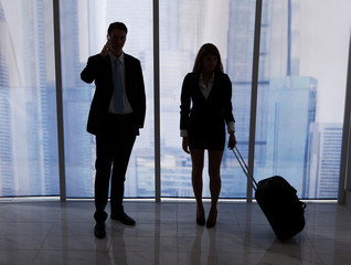 Businessman On Call Standing By Colleague With Luggage In Office