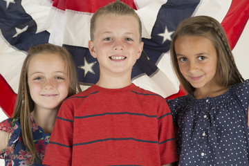 patriotic children standing in front of a flag banner