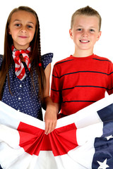 American girl and boy holding patriotic banner smiling