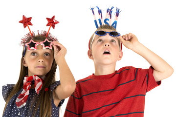 boy and girl looking up at fireworks wearing patriotic glasses