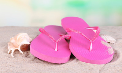 Bright flip-flops on sand, on nature background