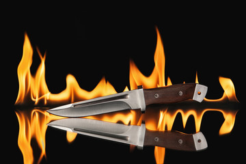 Hunting knife with fire on a black background