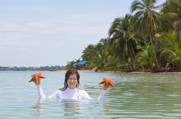 Woman with two starfish in hands, Panama