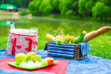Photo sur Aluminium Pique-nique Picnic basket with fruits, bread and bottle of white wine