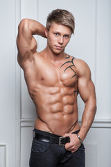 Muscular young naked sexy man posing in jeans