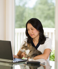 Mature woman relaxing with her cat while working at home
