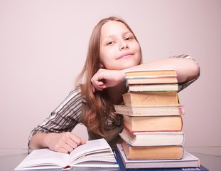 Happy teen girl sitting with books