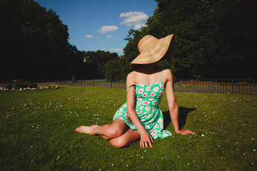 Young woman wearing hat and dress sitting in park