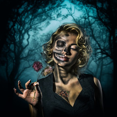 Retro woman with skull make-up and dried flowers