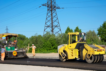 Workers with rolling machinery making asphalt