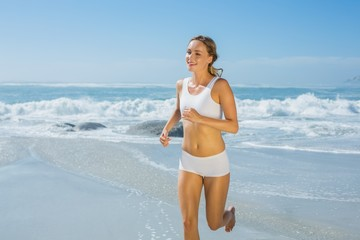 Gorgeous fit blonde jogging by the sea