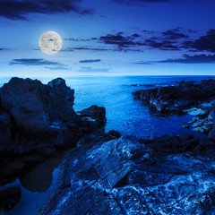 calm sea wave touches boulders at night