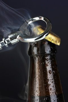 Top of open wet beer bottle on dark background