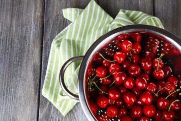 Sweet cherries in colander on color wooden background