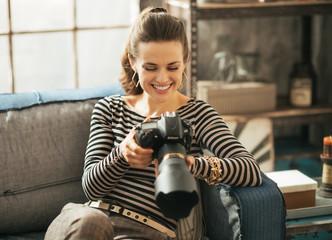 Happy woman sitting on divan and using modern dslr photo camera
