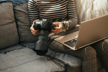 Closeup on woman with laptop using modern dslr photo camera