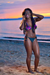 Beautiful black African American woman posing on the beach at su