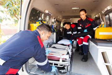paramedics taking stretcher out of an ambulance