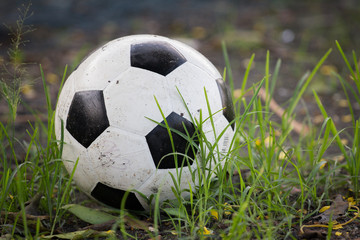 Battered old soccer ball, slightly deflated, in long grass of un