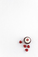 close up chocolate cup cake and rasberry on white fabric
