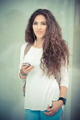 beautiful curly long brunette hair moroccan woman using smart ph