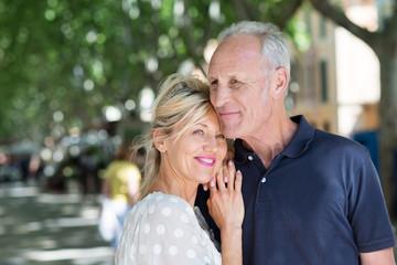 glückliches seniorenpaar in der stadt unter bäumen