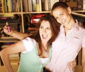 two cute girlfriends taking photo of themselves