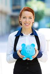 Portrait happy woman, corporate employee holding piggy bank