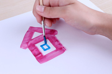 Child draws house with watercolors, close up
