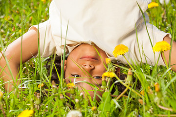 Cute curly boy stands upside down in field