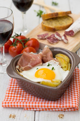 Spanish traditional dish fried eggs with serrano ham and potatoe