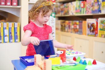 Little pretty girl in crown of princess plays with toys in store