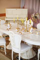 Table with set of porcelain dishes and lighted candles