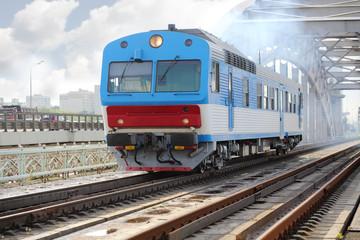 Small blue train rides rails on railway bridge at summer day.