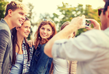 teenagers taking photo with digital camera outside