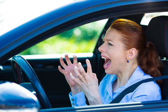 Angry female driver in her car, screaming at someone