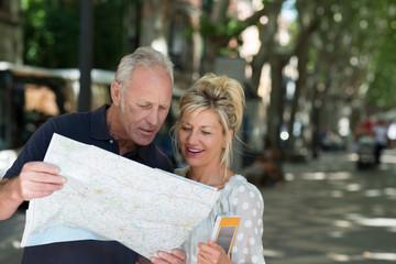 älteres paar in der stadt schaut auf karte