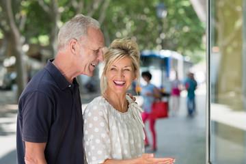 lachendes älteres paar vor einem schaufenster