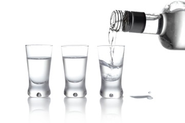 Bottle and glasses of vodka poured into a glass isolated on whit