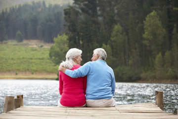Printed kitchen splashbacks Fishing Senior couple sitting on a jetty