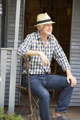 Mid age man resting on veranda