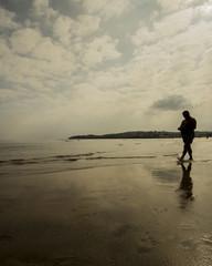 Anciano paseando por la playa